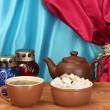 图库照片: Teapot with cup and saucer with sweet turkish delight on wooden table on a background of curtain close-up