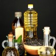Olive and sunflower oil in the bottles and small decanters isolated on black background close-up - Stock Photo