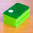Stock Photo: Sponge with dishwashing liquid on wooden table