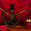 Hookah on a wooden table on a background of red curtain close-up - Стоковая фотография