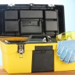 Open yellow tool box with tools  on blue background close-up — Stock Photo