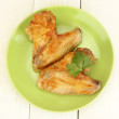 Roasted chicken wings with parsley in the plate on white wooden background close-up — Stock Photo #11655411