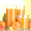 Glasses of apricot juice on yellow background — Stock Photo #11655458
