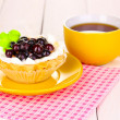 Sweet cake with cup of tea on wooden background — ストック写真