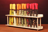 Various spices in tubes on wooden table on red background — Stock Photo