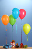 Colorful balloons holding a gifts on a wooden table on blue background — Stock Photo