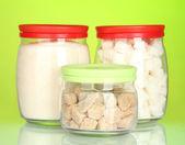 Gläser mit braunen Rohrzucker Klumpen, weißen Kristallzucker und weißen Würfelzucker isoliert auf weiss — Stockfoto