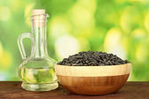 Sunflower oil in small decanter with sunflower seeds on green background close-up — Stock Photo