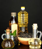 Olive and sunflower oil in the bottles and small decanters isolated on black background close-up — Stock Photo