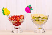 Mixed fruits and berries in glasses on wooden background — Stock Photo