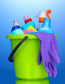 Bucket with cleaning items on blue background — Stock Photo