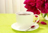 Kubek gorącej czekolady i kwiaty na stole w kawiarni — Zdjęcie stockowe