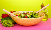 Fresh salad with tomatoes and cucumbers on green background — Stock Photo