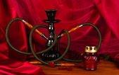 Hookah on a wooden table on a background of red curtain close-up — Stock Photo