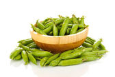 Green peas in wooden bowl isolated on white — Stock Photo