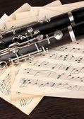 Muzieknoten en klarinet op houten tafel — Stockfoto