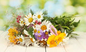 Beautiful bouquet of bright wildflowers, on wooden table on green background — Stock Photo