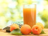 Szkło sok z moreli i świeże morele na drewnianym stole na zielonym tle — Zdjęcie stockowe