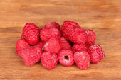 Fresh raspberries on wooden background close-up — Stock Photo