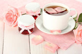 Cup of tea with roses and jam on white wooden table — Stock Photo