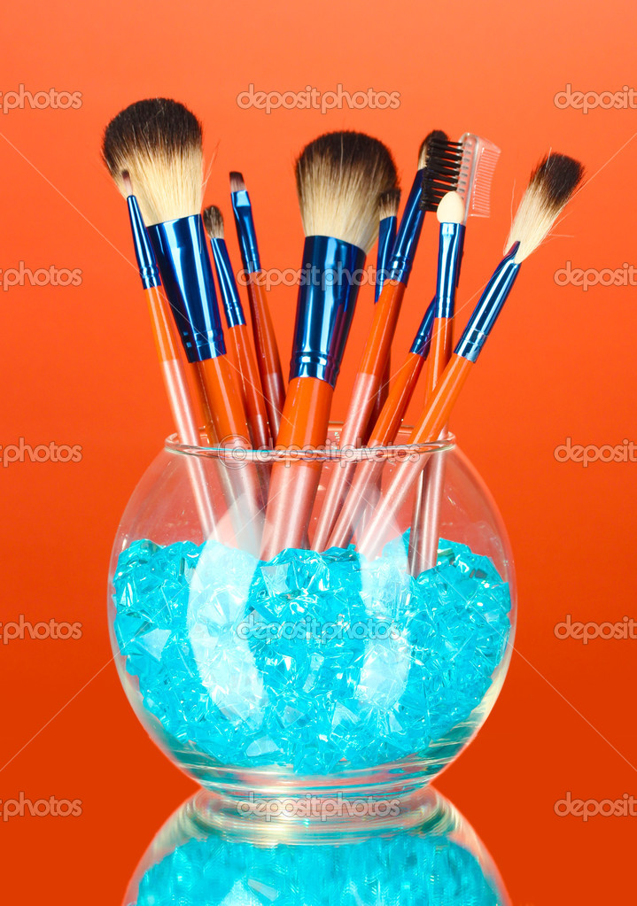 Make-up brushes in a bowl with stones on red background — Stock Photo #11655763