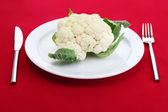 Fresh cauliflower on plate, knife and fork — Stock Photo