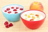 Yogurt con duraznos y frambuesas en tazones en estera de bambú — Foto de Stock