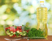 Fresh salad and oil on green background — Stock fotografie