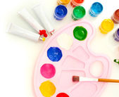 Tubes with colorful watercolors and jars with gouache and palette on white background close-up — Stock Photo