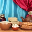 Teapot with cup and saucers with oriental sweets - sherbet, halva and turkish delight on wooden table on a background of curtain close-up - Stock Photo