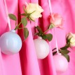 Beautiful roses in vases hanging on cloth background — Lizenzfreies Foto