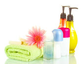 Cosmetics bottles with towels and flower isolated on white — Stock Photo