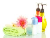 Botellas de cosméticos con toallas y flor aislado en blanco — Foto de Stock