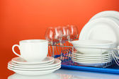 Clean dishes on stand on red background — ストック写真