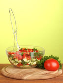 Fresh salad on green background — Stock Photo