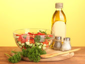 Fresh salad and oil on green background — Stok fotoğraf