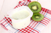 Yogurt with kiwi on napkin on wooden background — Stock Photo