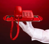 Hand in glove holding silver tray with telephone on red background — Стоковое фото