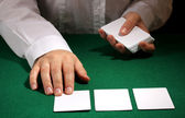 Cards in hands on green table — Stock Photo