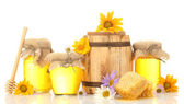Sweet honey in jars and barrel with honeycomb, wooden drizzler and flowers isolated on white — Stock Photo
