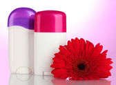 Deodorants with flower on pink background — Stock Photo