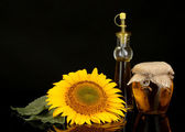 Sunflower oil and sunflower isolated on black — Stock Photo