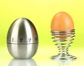 Egg timer and egg in metal stand on green background — Stock Photo