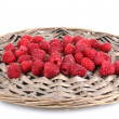 Photo: Raspberries on wicker mat isolated on white
