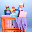 Basket with cleaning items on blue background — Stock Photo #11706304