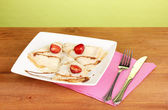 Stack of tasty pancakes on wooden table on green background — Stock Photo