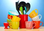 明亮的空碗、 杯子和在蓝色背景上的木桌上的厨房用具 — 图库照片