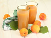 Glasses of apricot juice and fresh apricots on white wooden table — Stock Photo