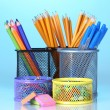 Color holders for office supplies with them on bright background - Stock Photo