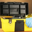 Open yellow tool box with tools  on brown background close-up - Stock Photo